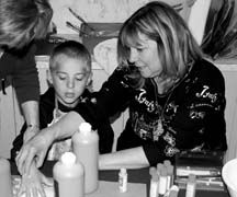 HANDPRINT QUILT: Ricky Hodgins, 5, has fun making his own handprint under the watchful eye of teacher Janice Taylor.