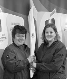 Bearing the torch: Joyce Carlson and Kim Barrows hold an Olympic torch aloft in anticipation of the February 3 event.