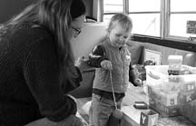 OUTSIDE THE BOX: Amanda Zaikow and her son Reed Worthen play with alphabet boxes on board the ORCA bus. (Photo by Bonnie Krakalovich)